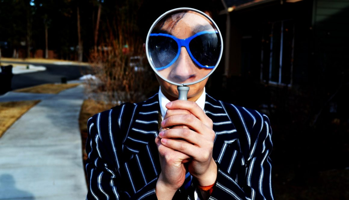 Man in pinstripe suit holding a magnifying glass to his face to ask what is SEO