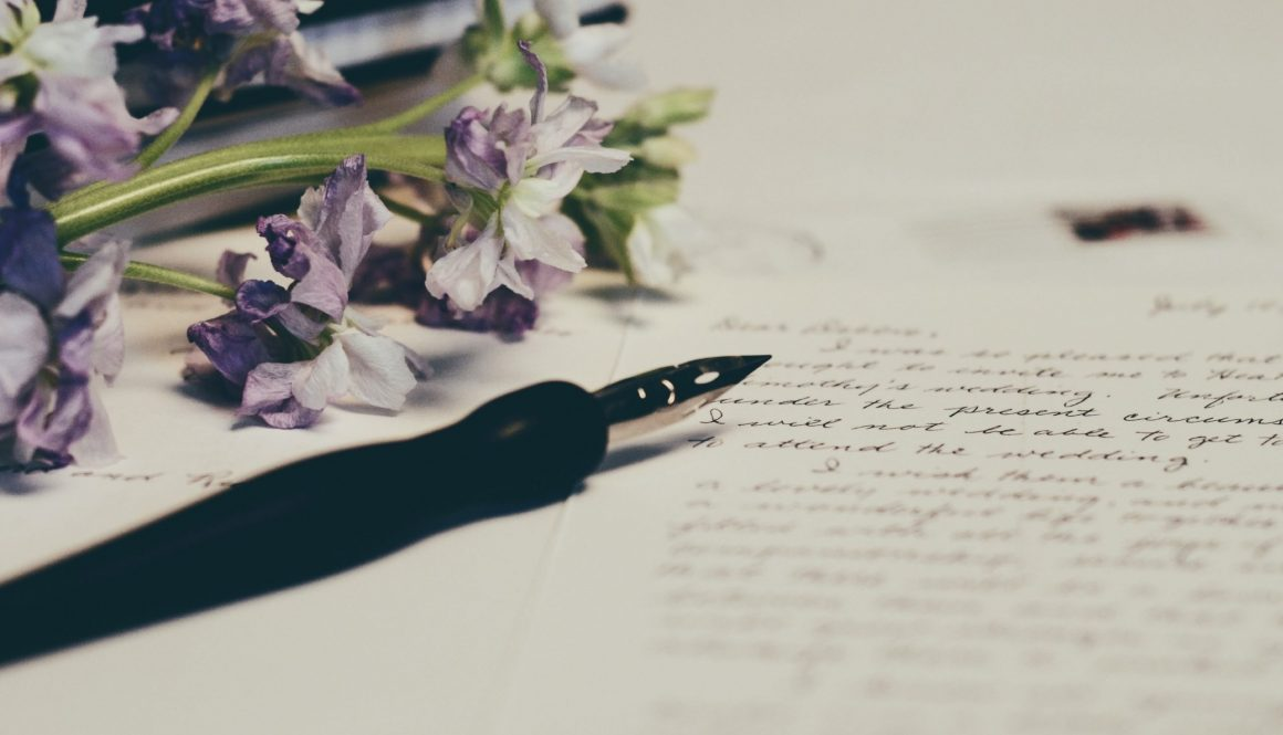 pen and purple flowers on a white table with writing about SEO for wellbeing blogs